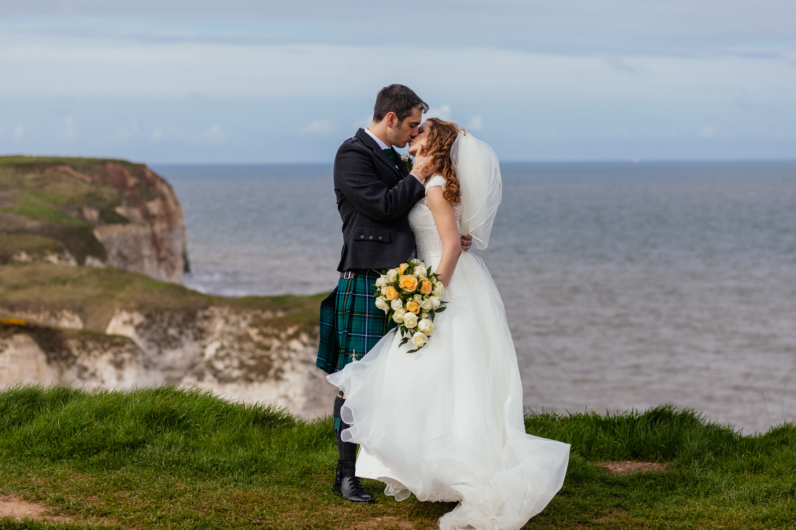 bride-and-groom-standing-on-cliffs-at-flamborough