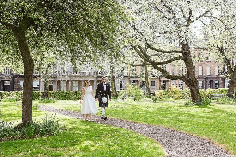 bride-and-groom-walk-hand-in-hand-through-private-garden-in-edinburgh